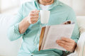 Close up of man with magazine drinking from cup home rest news drinks and people concept reading and sitting on couch at home Stock Images