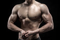 Close up of man model torso posing showing perfect body and shoulders biceps triceps and chest on black background Royalty Free Stock Photo