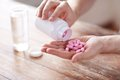 Close up of man pouring pills from jar to hand Royalty Free Stock Photo