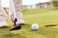 Close up of man putting ball into hole Royalty Free Stock Photo
