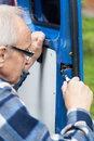 Close up of a man repairing car door gray haired Stock Photos