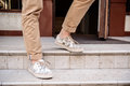 Close up of man's legs in keds going down stairs. Royalty Free Stock Photo