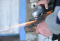 Close up of a man sharpen an ax using electric grinder sparks while grinding iron selective focus Stock Photo