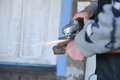 Close up of a man sharpen an ax using electric grinder sparks while grinding iron selective focus Stock Photography