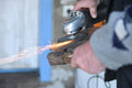 Close up of a man sharpen an ax using electric grinder sparks while grinding iron selective focus Royalty Free Stock Photos