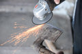 Close up of a man sharpen an ax using electric grinder sparks while grinding iron selective focus Royalty Free Stock Photo