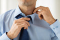 Close up of man in shirt adjusting tie on neck Royalty Free Stock Photo