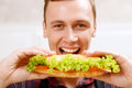 Close up man taking bite of sandwich so tasty young smiling big tasty Stock Photos