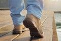 Close up on man wearing lumberjack boots walking on dock strong rugged male style hunter fisherman adventure man Stock Photo