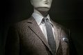 Close up of a mannequin in a brown checkered jacket with white shirt grey tie and striped blue white handkerchief on black Royalty Free Stock Image