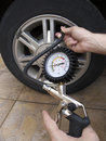 Close up of manometer and man hands checking tire pressure with gauge Royalty Free Stock Image