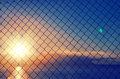 Close up of mesh fence against the blurred sunset sky. Abstract blue orange background
