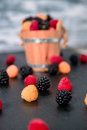 Close up of mixed red, black, yellow raspberries on  table with basket  backround. Royalty Free Stock Photo