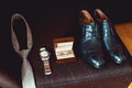 Close up of modern groom accessories. wedding rings in a brown wooden box, necktie, leather shoes and watch