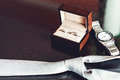 Close up of modern groom accessories. wedding rings in a brown wooden box, necktie and watch