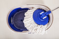 Close up of mop and blue bucket for cleaning floor Royalty Free Stock Photo