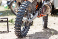 Close-up of muddy rear wheel and engine of dirt motorcycle Royalty Free Stock Photo