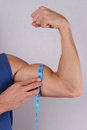 Close up of muscular man measuring biceps with tape measure. Bodybuilding, Fitness, port challenge concept Royalty Free Stock Photo