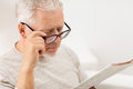Close up of old man in glasses reading newspaper Royalty Free Stock Photo