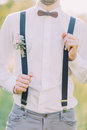 The close-up outlook of the groom in the white shirt, gray pants, suspenders with the flower accessories and wooden