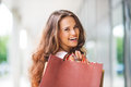 Close up over the shoulder smiling brown haired woman shopping a holding bags with a textured bag most prominent her right looks Royalty Free Stock Photos