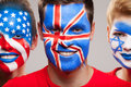 Close up of painted faces three person with diffrent contries flag on their Royalty Free Stock Photography
