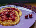 Close up of pancakes with cherry jam delicious on a table surrounded by purple flowers Royalty Free Stock Photos