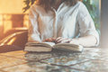 Close-up of paper book, notebook, diary on table in cafe. Businesswoman in white shirt sitting at table and reading book Royalty Free Stock Photo