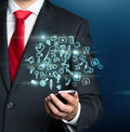 Close-up of a person in a formal suit who holds a smartphone with glowing mobile app icons. Royalty Free Stock Photo