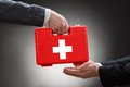 Close up of a person s hand giving first aid box to another Royalty Free Stock Image