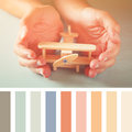 Close up photo of man's hand holding wooden toy airplane over wooden background. vintage filter with palette color swatches