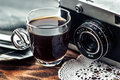 Close up photo of old, vintage camera lens with cap of coffee and black and white photos over wooden table. Royalty Free Stock Photo