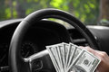 Close-up of american dollars on a wheel. A man driving with money on a car background. Investment and savings concept. Royalty Free Stock Photo