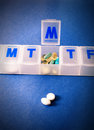 Close up pills dispenser blue background Stock Image