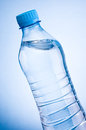 Close up plastic bottle of drinking water obliquely on a blue background Royalty Free Stock Photography
