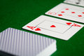 Close up of playing cards on green table surface Royalty Free Stock Photo