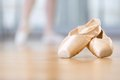 Close up of pointes for ballet lying on the wooden floor in classroom Royalty Free Stock Photo