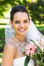 Close-up portrait of a beautiful bride with bouquet in park Royalty Free Stock Photo