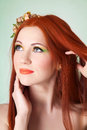 Close-up portrait of beautiful red-haired girl with flowers in hair Royalty Free Stock Photo