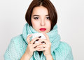 Close-up portrait of beautiful woman in a woolen scarf, drinking hot tea or coffee from white cup Royalty Free Stock Photo