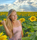 Close up portrait of a beautiful young girl in pink dress in a field of sunflowers Royalty Free Stock Photo