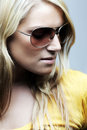 Close up portrait of blond woman with sunglasses a beautiful wearing and a serious expression Royalty Free Stock Images