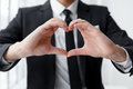 Close up of portrait of businessman making a heart with his hands. Royalty Free Stock Photo