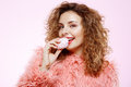 Close up portrait of cheerful smiling beautiful brunette curly girl in pink fur coat eating marshmallow over white Royalty Free Stock Photo