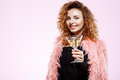 Close up portrait of cheerful smiling beautiful brunette curly girl in pink fur coat holding cocktail glass over white Royalty Free Stock Photo