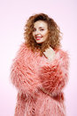 Close up portrait of cheerful smiling beautiful brunette curly girl in pink fur coat over white background. Royalty Free Stock Photo