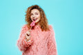 Close up portrait of cheerful smiling beautiful brunette curly girl in pink fur coateating lollipop over blue background Royalty Free Stock Photo