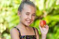 Close up portrait cute girl holding red apple outdoors Stock Photography