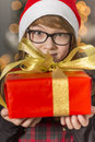 Close-up portrait of cute girl holding wrapped Christmas present Royalty Free Stock Photo