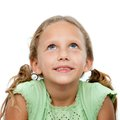 Close up portrait of cute girl looking up. Royalty Free Stock Photo